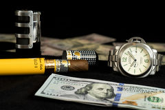 Luxury watch with an cuban cigar laying next to 100 dollar bills Stock Images