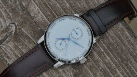 Luxury watch with a leather strap on a black background stock footage
