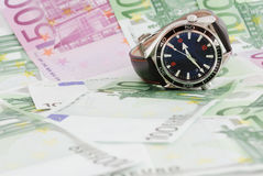 Luxury watch on money. Luxury wristwatch with a background of paper money (Euros Stock Image