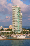 Luxury waterfront apartment building. Highrise apartment building located at waterfront with adjacent marina with boats Royalty Free Stock Images
