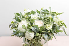 Luxury wedding bridal bouquet with white peonies and mixed flowers on pink dresser Royalty Free Stock Photo