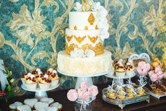 Luxury wedding candy bar with a beautiful white cake decorated with gold ornaments. Concept of chic wedding desserts Stock Image