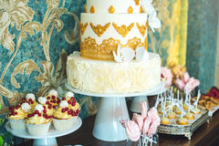 Luxury wedding candy bar with a beautiful white cake decorated with gold ornaments. Concept of chic wedding desserts Royalty Free Stock Photo