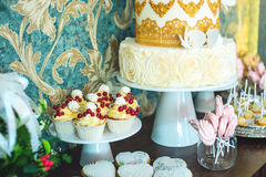 Luxury wedding candy bar with a beautiful white cake decorated with gold ornaments. Concept of chic wedding desserts Stock Images