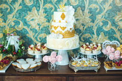 Luxury wedding candy bar with a beautiful white cake decorated with gold ornaments. Concept of chic wedding desserts Stock Photo