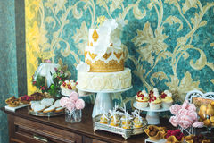 Luxury wedding candy bar with a beautiful white cake decorated with gold ornaments. Concept of chic wedding desserts Royalty Free Stock Images