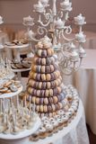 Luxury wedding candy bar table set. Macaron tower or pyramid and cupcakes on sweet dessert table. Pastel stylish colours., sweets, treats stock image