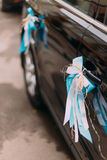 Luxury wedding car decorated with white and blue ribbons Royalty Free Stock Photos