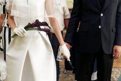 Luxury wedding couple holding hands closeup with calla bouquet i Stock Photos