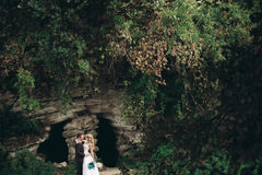 Luxury wedding couple hugging and kissing on the background gorgeous plants and cave near ancient castle Royalty Free Stock Photos