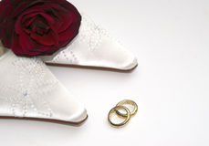 Luxury Wedding day. Beautiful satin bridal shoes and red rose with gold engraved wedding rings for a luxury and special wedding day Royalty Free Stock Photography