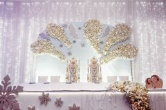 Luxury wedding decor arrangements of centerpiece table for bride. And groom. royal chairs with flower decorations. expensive catering. space for text. wedding Stock Image