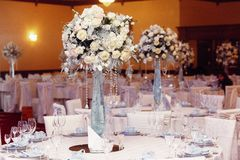 Luxury wedding decor with flowers and glass vases with jewels on Stock Images