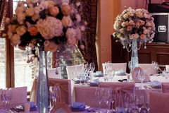 Luxury wedding decor with flowers and glass vases with jewels on Royalty Free Stock Image
