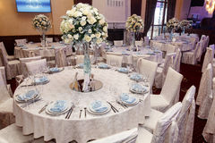 Luxury wedding decor with flowers and glass vases with jewels on. Round tables. arrangements of decorations at wedding reception. expensive catering. space for Stock Photos