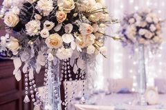 Luxury wedding decor with flowers of roses and hydrangea closeup. In glass vases with jewels. arrangements decorations at wedding reception. expensive catering Stock Photos