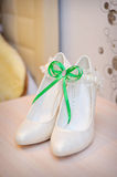 Luxury wedding shoes. Elegant bridal shoes and a white garter Stock Photography