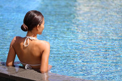 Luxury wellness spa retreat woman relaxing in pool. Luxury travel wellness resort bikini woman relaxing in swimming pool. Hydrotherapy spa retreat from behind on royalty free stock photos