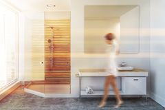 Luxury white bathroom sink and shower, woman. Woman in a luxury bathroom interior with a wooden shower stall, a sink vanity unit and a large mirror. 3d rendering royalty free stock image