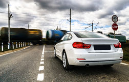 Luxury white car waiting at the railway crossing Royalty Free Stock Photo