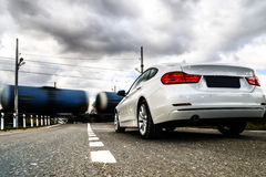 Luxury white car waiting at the railway crossing Stock Photography