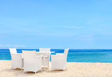 Luxury white chairs and table on white sandy beach. With a view of blue ocean and clear sky on a bright sunny day royalty free stock image