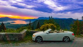 Luxury white convertible on the background of the sunset sky in the mountains royalty free stock photo