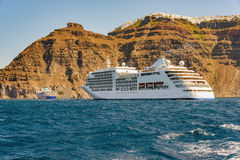 Luxury white cruise ship near high rocks on the greek island of Santorini Stock Images