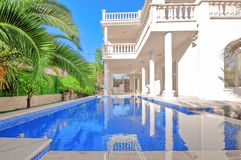 Luxury white house with swimming pool. Luxury villa in classica. L style with columns. Backyard with swimming pool in mansion stock image