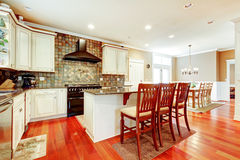 Luxury white kitchen with cherry hardwood and island with chairs. Royalty Free Stock Photo