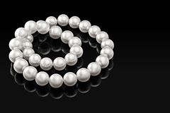 Luxury white pearl necklace on a black background with glossy reflection Stock Images