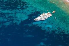 Luxury white pleasure yacht near rocky coast Royalty Free Stock Photos