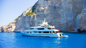 Luxury white yacht navigates into beautiful blue water near Zakynthos Island, Greece. View from the top of a large white yacht at Navagio Beach royalty free stock photography