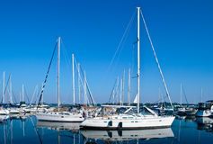 Luxury white yachts and boats moored in harbour stock images