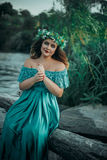 Luxury witch in a long green dress  for lake Royalty Free Stock Photography