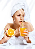 Luxury woman after bath in white bathrobe and towel on her head drinking orange juice. royalty free stock photos