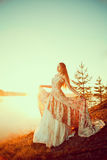 Luxury woman in a forest in a long vintage dress near the lake. Stock Photography