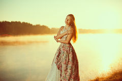 Luxury woman in a forest in a long vintage dress near the lake. Stock Image