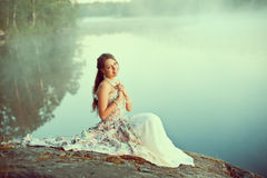 Luxury woman in a forest in a long vintage dress near the lake. Royalty Free Stock Images