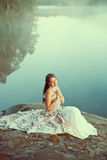 Luxury woman in a forest in a long vintage dress near the lake. Royalty Free Stock Photography
