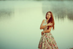 Luxury woman in a forest in a long vintage dress near the lake. Royalty Free Stock Photos