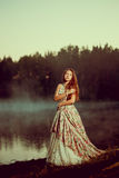 Luxury woman in a forest in a long vintage dress near the lake. Stock Photo