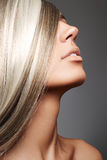Luxury woman with long blond hair. Beautiful woman with long blond hair on gray background Royalty Free Stock Images