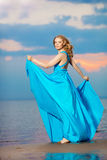 Luxury woman in a long blue evening  dress on the beach. Beauty Stock Images