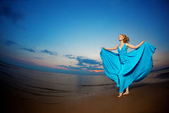 Luxury woman in a long blue evening  dress on the beach. Beauty Royalty Free Stock Image