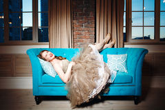 Luxury Woman Lying on Blue Couch Royalty Free Stock Photos