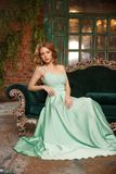 Luxury woman model in a mint-colored dress sitting on a vintage couch. Beauty girl with a stunning makeup and hairstyle royalty free stock images