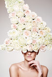 Luxury woman with a rose hat in fashion model pose. Luxury woman with a big rose hat in fashion model pose on gray background Stock Photos