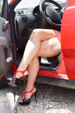 Luxury woman with sexy legs in car Stock Image