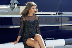 Luxury woman is sitting near boat Stock Photos